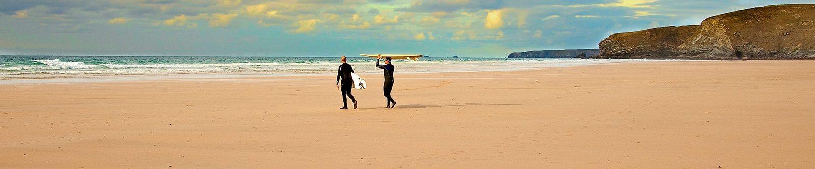 surfers walking to sea