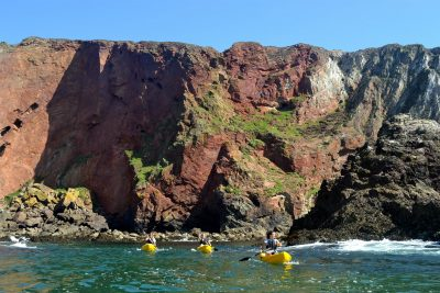 kayakers by cliffs