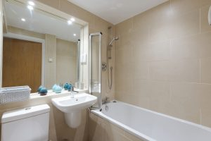 Bath with overhead shower and basin