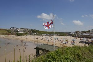 RNLI flag and bathers enjoying the beach and sea
