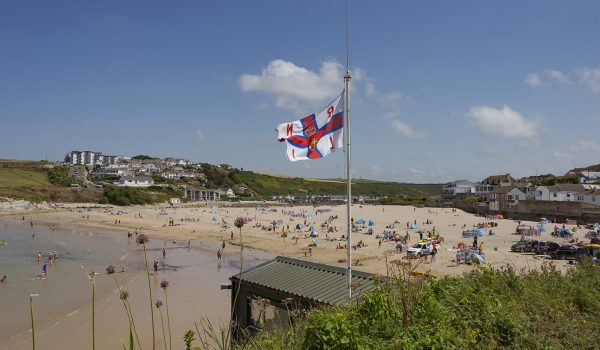 RNLI flag and bathers enjoying the beach and sea